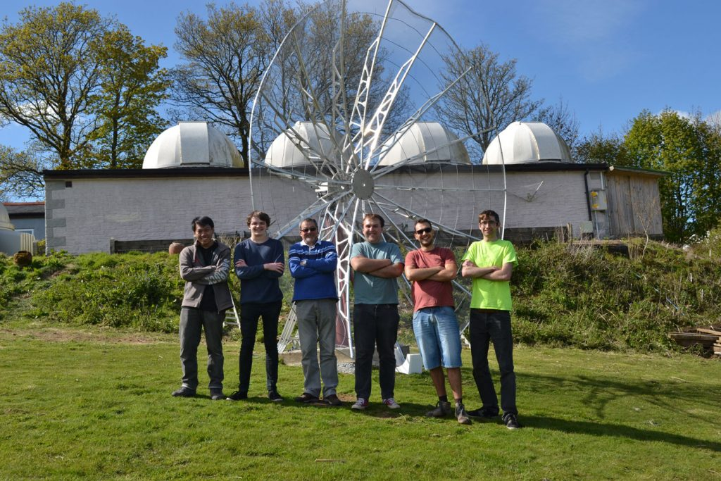 The build team, along with Caradon Observatory owner Ken Bennett, stand in front the newly mounted dish after a hard days work.